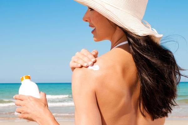 Frau cremt sich am Strand mit Sonnencreme ein